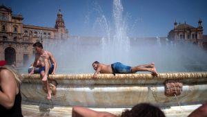 Ihmiset vilvoittelivat suihkulähteessä Sevillassa, Espanjassa 13. heinäkuuta.