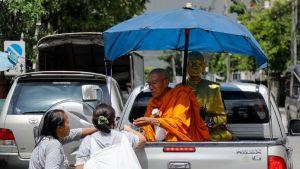 Buddhalaismunkki antaa siunauksensa ohikulkijoille Bangkokissa.