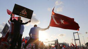 Ihmiset heiluttavat Turkin lippuja Bosporin sillalla Istanbulissa Turkissa.