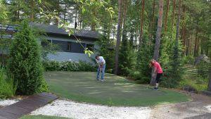 Mies ja nainen kotipihalle rakennetulla golfviheriöllä puttaamassa