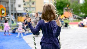 Tyttökeinuu seisoalleen leikkipuiston keinussa.