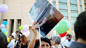 Turkkilaisnainen kantoi kädessään vangitun toimittajan Ahmet Sikin kuvaa.