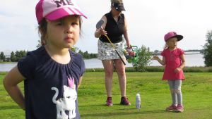 Lapsia ja aikuinen golfkentällä