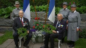 Sotaveteraaneja pitelemässä havuseppeleitä, lottapukuisia naisia ja Suomen liput