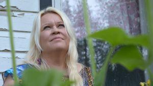 Hanna Ikonen katsoo ylös taivaalle. Edessä viherkasveja.