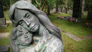 Äiti-lapsi -patsas hautausmaalla.