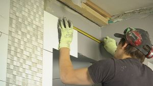 Mies laatoittaa seinää