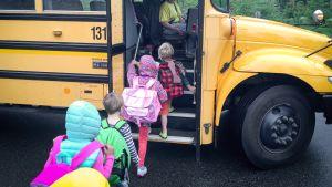 Lapset nousevat koulubussiin Yhdysvalloissa.