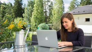 Nainen istuu terassilla tietokoneen ääressä.