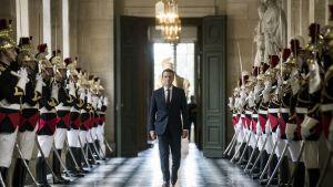 Tiukkailmeinen Macron kävelee sotilaiden välissä.