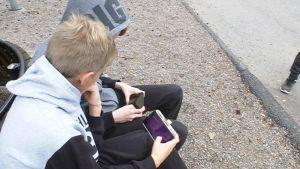 Koululaisia kännykät kädessä