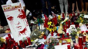 Uhrien muistoksi jätettyjä kynttilöitä ja kukkia sekä kyltti, jossa lukee Rukoilkaa Barcelonan puolesta.