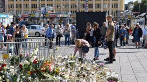 ihmisiä jättämässä kukkia torin muistopaikalle