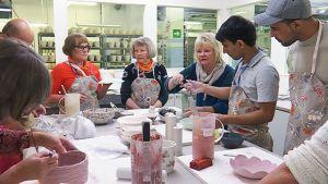 Anu Pentik opastaa  irakilaisia turvapaikanhakijoita ja posiolaisia työpajaan osallistuvia tekemään yksilöllistä keramiikaa.