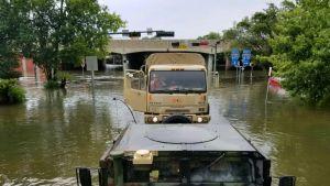 Sotilaita kuorma-autossa veden peittämällä tiellä.