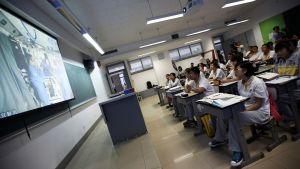 Kiinalaiset opiskelijat katselevat ohjelmaa kiinan avaruusohjelmasta.
