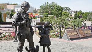Patsas esittää asetta olallaan kantavaa hymyilevää sotilasta ja tyttöä, joka ojentaa hänelle kukkapuskaa.