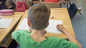 Oppilas istuu pulpetissa ja harjoittelee kirjoittamista.