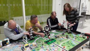 legorobotteja pöydällä, ihmisiä ympärillä