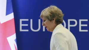 """Valkoiseen jakkuun pukeutuneen Theresa May sivuprofiili takana teksti """"europe""""."""