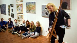Savonlinnan normaalikoulun kahdeksasluokkalaiset tarkkailevat kuvataiteilija Joni Ahosta työssään.