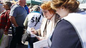 Nainen allekirjoittaa Sauli Niinistön kampanjan kannattajakortin Hakaniemen maalaismarkkinoilla Hakaniemessä, Helsingissä.