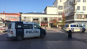Kaksi poliisiautoa torilla.