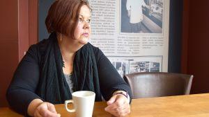 Nainen istuu kahvilassa ja katsoo ikkunasta ulos