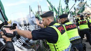 Poliisi estää mielenosoittajia marssimasta kielletylle kaduille.
