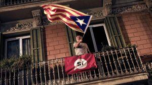 Mies heilutti Katalonian itsenäisyyttä tukevaa Estelada-lippua äänestyspaikan sulkeuduttua 1. lokakuuta Barcelonassa.
