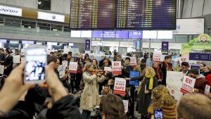 ihmisiä lentoasemalla plakaateja käsiissään ja viulua soittava nainen