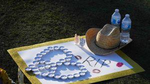 Cowboy-hattu, kaksi vesipulloa, numerot 59 ja kynttilöistä muotoiltu sydän kultareunaisen uhreille omistetun muistokortin päällä Las Vegasin Stripillä.