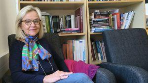 Kirjailija Hanne Dahl kirjahyllyn edessä.