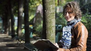 Nainen istuu puistonpenkillä.