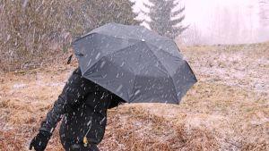 Nainen kävelee lumisateessa.