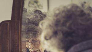 Vanhempi nainen siirtelee tavaroita peilipiirongin päällä ja hänen kasvonsa heijastuvat peilin kautta kohti kameraa.