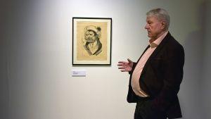 Mies tutkii litografia, joka on ripustettu taidemuseon seinälle