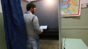 Kuvassa nuorehko mies antaa äänensä äänestyskopissa.
