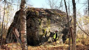 Yle Oulun toimittaja Arto Veräjänkorva ihmettelee Pyhäjoen Hanhikiven suurta kokoa. Kivi on noin kuusi metriä korkea.