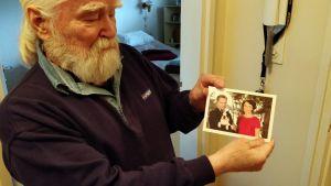Vanhempi mies pitää käsissään presidenttiparin kiitoskorttia.