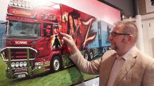 Mies esittelee maalattua kuorma-autoa
