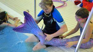 Nainen korjaa tytön merenneitopyrstöä uima-altaan reunalla