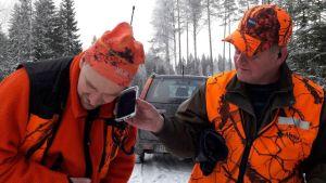 Kaksi metsästäjää kuuntele kännykästä koiran haukkua.