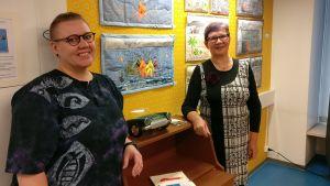 Nina Lappalainen ja Raili Kantola seisovat kankaisten sarjakuvaoriginaalien edessä näyttelytilassa.