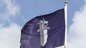 Liehuva lippu poliisin tunnuksella Tampereen poliisitalon edustalla.