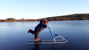 Pieni poika ajaa potkurilla lumettomalla jäällä.