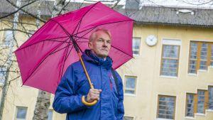 Mies seisoo sateessa sateenvarjon alla vanhan rakennuksen edessä.