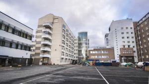 Vasemmalla oleva rakennus puretaan vuonna 2025 ja uusi lisäosa tulee parkkipaikan paikalle.