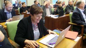Porin kaupunginjohtaja Aino-Maija Luukkonen Porin valtuustossa 13.11.2017, katsoo tietokonetta, on iloinen.