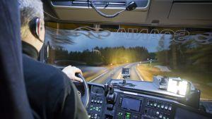 Kuorma-auton kuljettaja kuvattuna takaa auton hytistä pimeällä.
